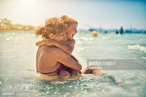 mother and son having fun in sea - candid beach stock photos and pictures