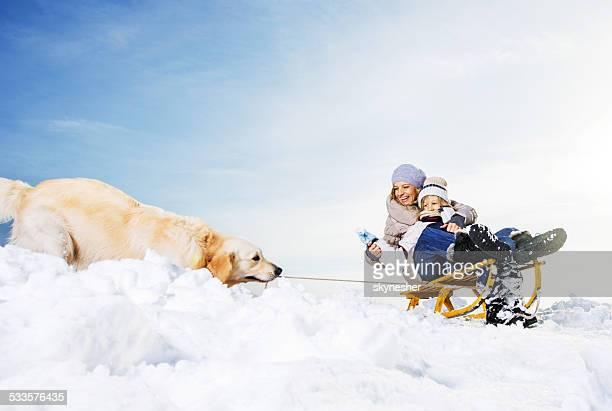 Mother and son having fun with dog on the snow.