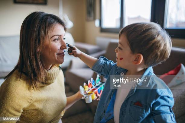mother and son having fun with finger paint - finger painting stock pictures, royalty-free photos & images