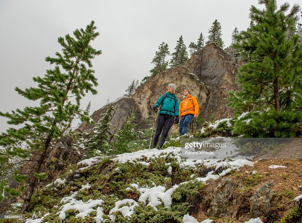 Mother and son hike on snowy mountainside : Stock Photo