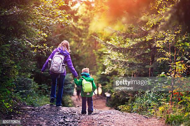 Mother and son hiking in forest.