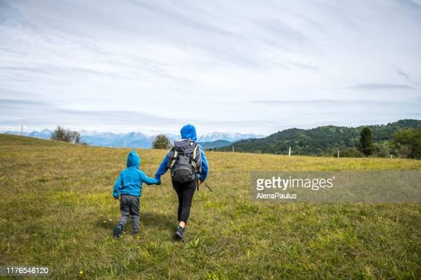 matriz e filho que caminham ao ar livre no platô verde com uma opinião bonita da montanha - planalto - fotografias e filmes do acervo