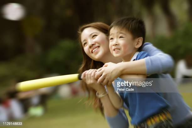 mother and son hitting ball with bat - batting sports activity stock pictures, royalty-free photos & images