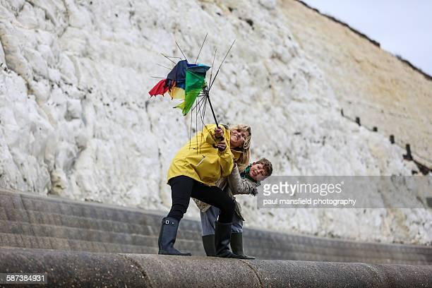 mother and son hold onto umbrella on windy day - virada ao contrário - fotografias e filmes do acervo