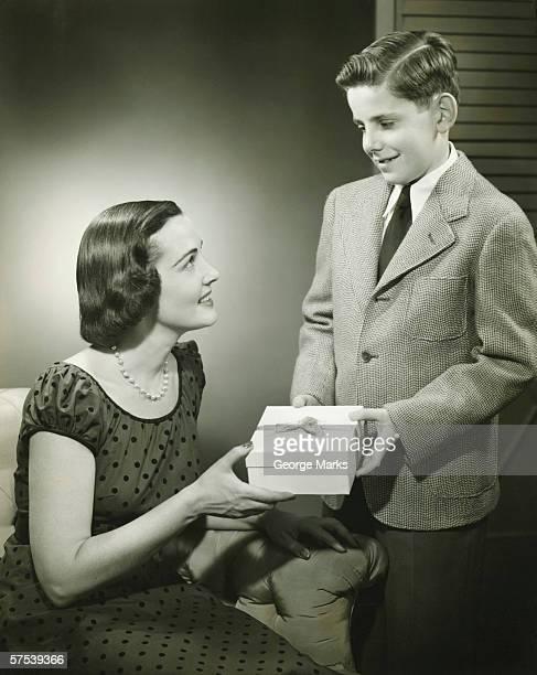 mother and son (12-13) holding beribboned box, (b&w) - 12 13 jaar stockfoto's en -beelden