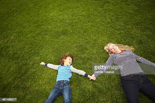 Mother and son holding hands and laying on grass