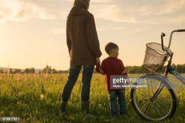 Mother and son holding hands in field near bicycle