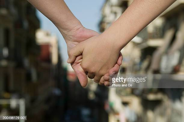 Mother and son (4-5) holding hands in street, close-up