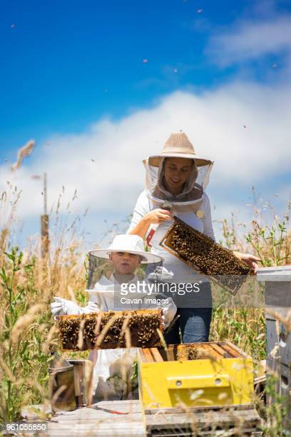 Mother and son holding honeycomb frames while standing against cloudy sky at field