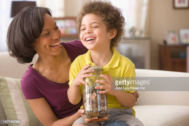 Mother and son holding jar of coins