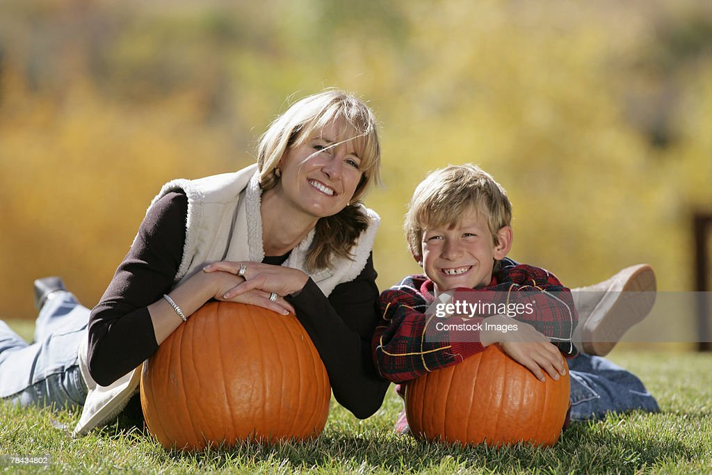 Mother and son holding pumpkins : Stockfoto