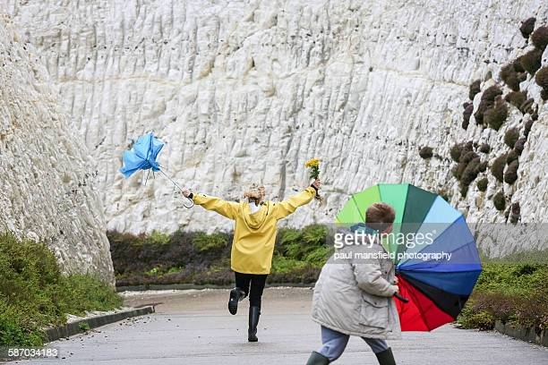 Mother and son holding umbrellas
