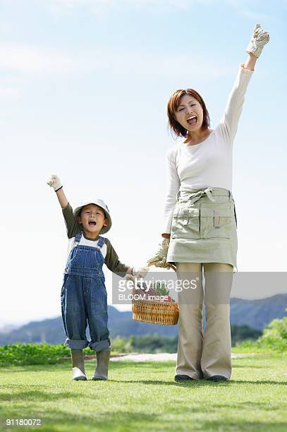 mother and son holding vegetables in basket, raising fists, portrait - ガッツポーズ ストックフォトと画像