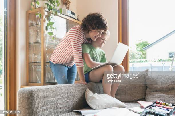 mother and son homeschooling using laptop - mindzoom 2 stock pictures, royalty-free photos & images