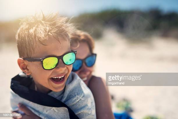 mother and son hugging and laughing on beach - sunglasses stock pictures, royalty-free photos & images