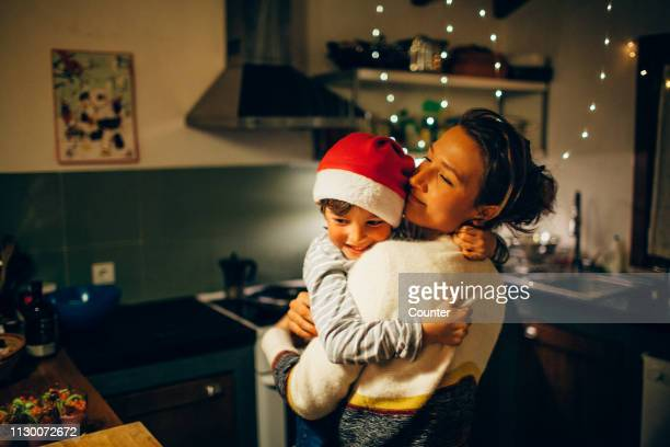 mother and son hugging in kitchen at christmas - taufpatin stock-fotos und bilder