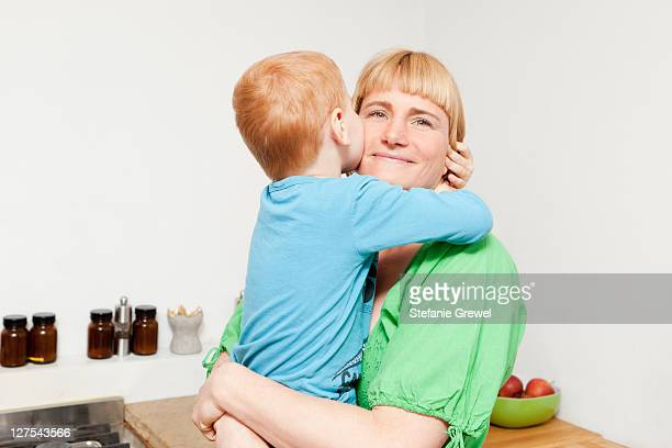 Mother and son hugging in kitchen