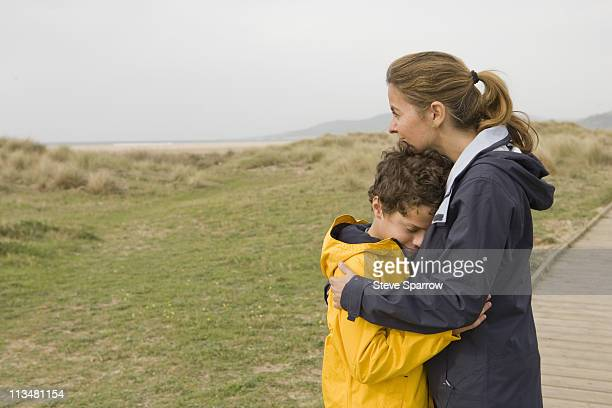 Mother and son hugging on boardwalk