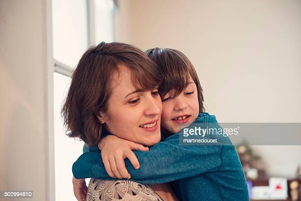 Mutter und Sohn umarmen küsst wie zu Hause fühlen.