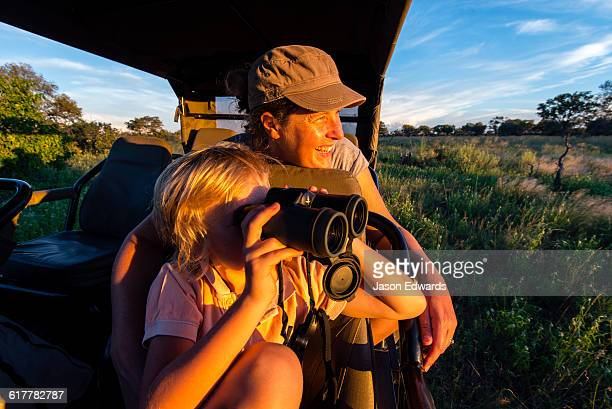 A mother and son in a safari 4wd watching wildlife.