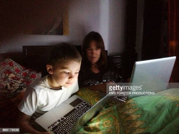 mother and son in bed using lap top computers
