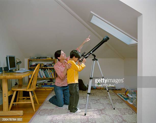 Mother and son in bedroom, boy using telescope, mother pointing