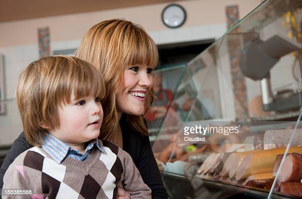 Mother and son in butchers shop
