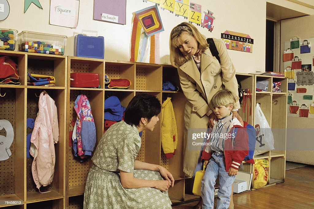 Mother and son in classroom meeting new teacher : Stock Photo