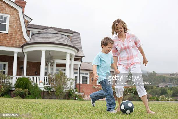 Mother and son in garden playing football