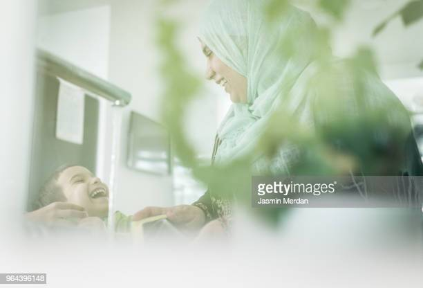 Mother and son in kitchen laughing