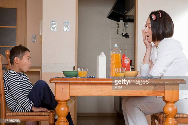 mother and son in pajama sitting at breakfast table - yawning mother child stock photos and pictures