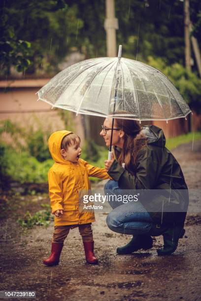 mother and son in raincoats under umbrella in rain - mother son shower stock photos and pictures