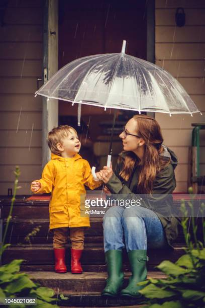mother and son in raincoats walking in rain - mother son shower stock photos and pictures