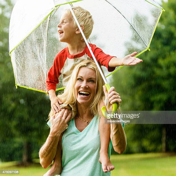mother and son in the rain. - mother son shower stock photos and pictures