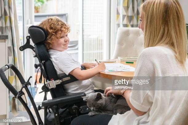 moeder en zoon in rolstoel met handicap thuis - disabilitycollection stockfoto's en -beelden