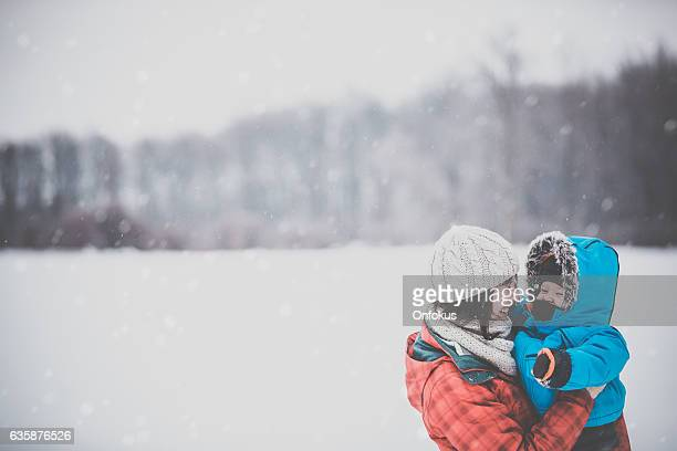 mother and son in winter forest snowstorm - day stock pictures, royalty-free photos & images