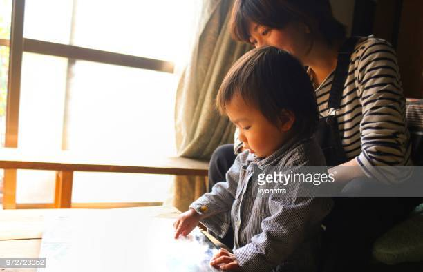 mother and son is making photo albam - childhood photo album stock photos and pictures