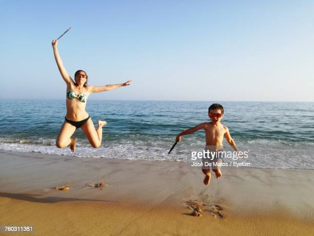 Mother And Son Jumping Against Sea At Beach