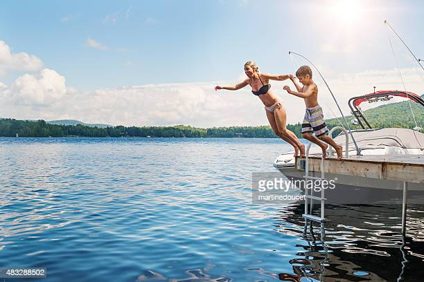 Mother and son jumping in lake from pier sunny day.