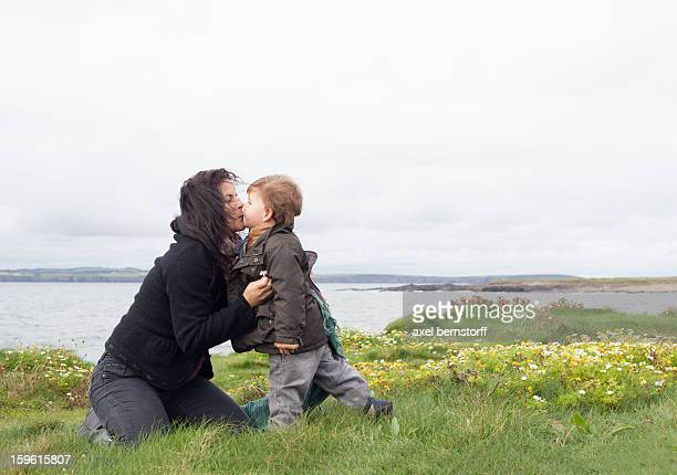 Mother and son kissing in grassy field