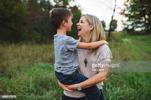 mother and son laughing and enjoying outdoors - single mother stock pictures, royalty-free photos & images