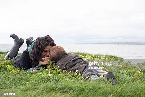 Mother and son laying in grassy field