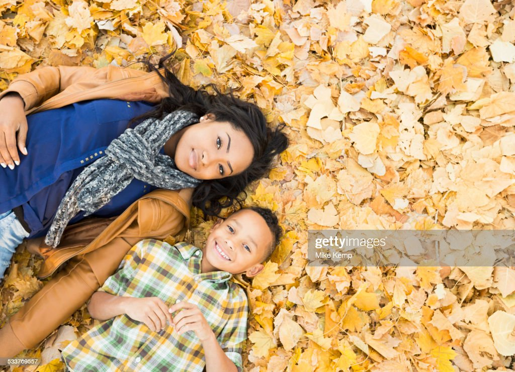 Mother and son laying together in autumn leaves : Foto stock