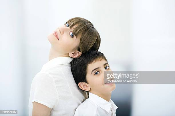 Mother and son leaning back to back, looking at camera, portrait