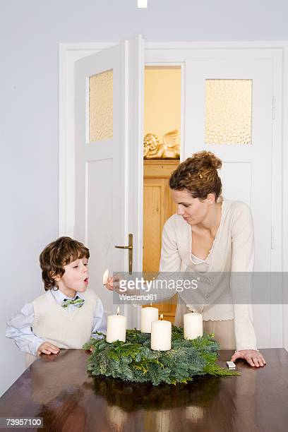 Mother and son (4-7) lighting Advent wreath