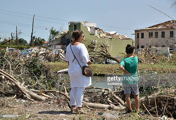A mother and son look at the damage caused by last night tornado on July 9 2015 in Venice Italy A tornado swept through the outskirts of Venice...