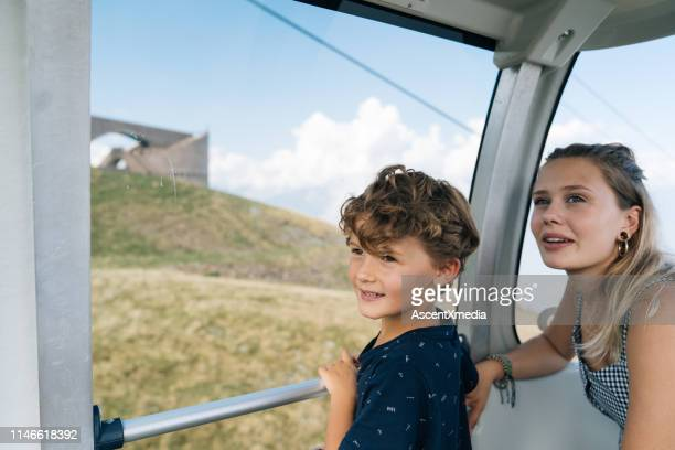mother and son look up while moving in gondola - ascent xmedia stock pictures, royalty-free photos & images