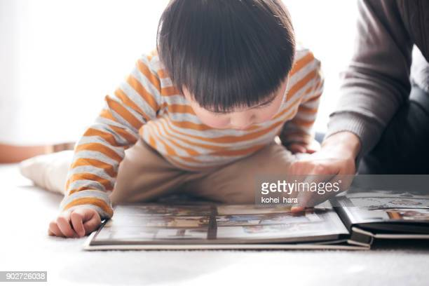 mother and son looking a photo album together - childhood photo album stock photos and pictures