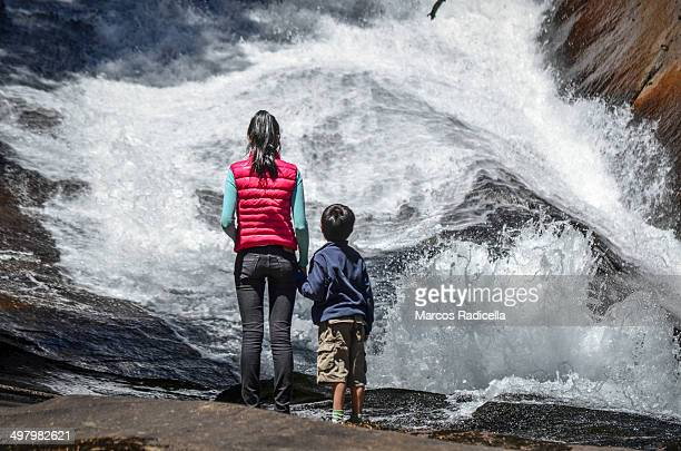 mother and son looking at a river flowing - radicella stock-fotos und bilder