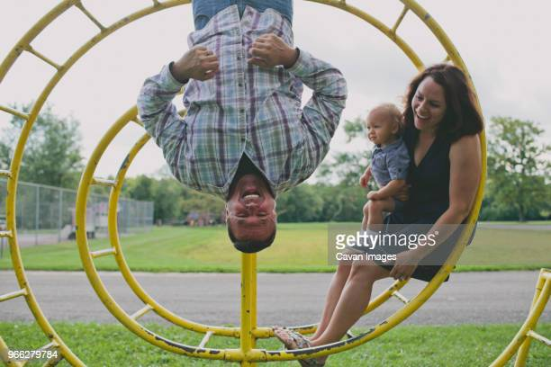 mother and son looking at father hanging on circular monkey bars in playground - cavan images foto e immagini stock
